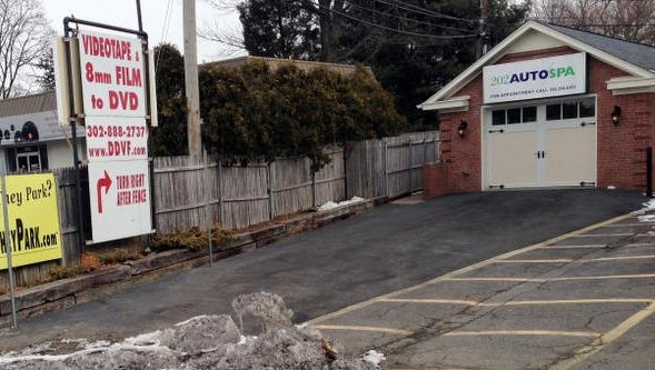 The Delaware Digital Video Factory has signs up on a fence facing their neighbor's business, the 202 Auto Spa, in Brandywine Hundred.