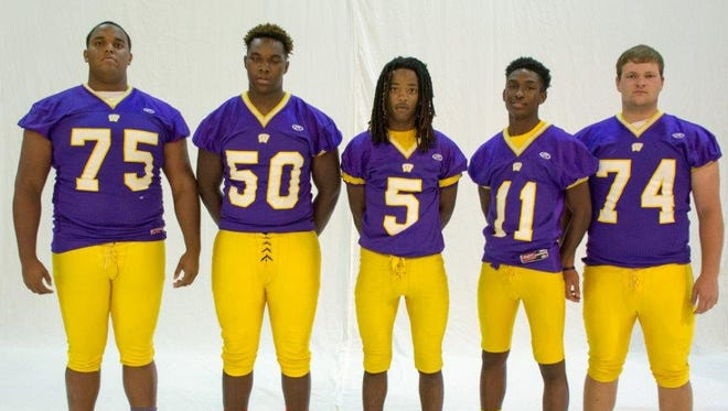 Westgate High offensive standouts guard Taylor Fondal (75), tackle Malik Mitchell (50), running back Trevon Doucet (5), wide receiver Phillip Tate and tackle Brody Robicheaux (74) line up during the Tigers' picture day.
