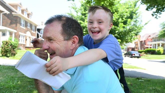 Alex Thornton, 9, climbs on father David Thornton's back while playing outside their Detroit home. The Thorntons want the city's school district to do better in providing special education services for Alex.