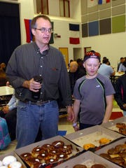 Nathan Brodjeski and his dad, Allen, look over assortment of doughnuts.