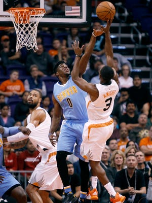 Denver Nuggets guard Emmanuel Mudiay (0) attempts to block the shot of Phoenix Suns' Brandon Knight during the first half of an NBA basketball game, Saturday, Nov. 14, 2015, in Phoenix.