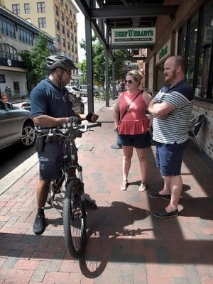 Pensacola Police Department Office Greg Gordon talks with Jamie and Jesse Hatter, of Stanford, Kentucky, on Friday, June 2, 2017, while he is out on bicycle patrol in the downtown area.