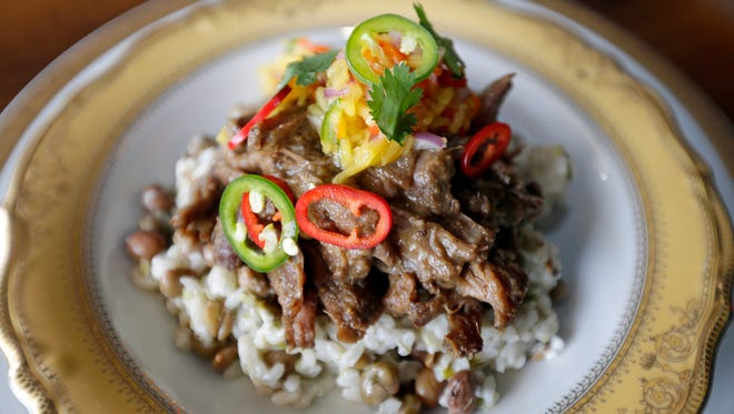 This Jamaican-style goat dish served at Meraki restaurant includes roasted goat, rice and pigeon peas and a mango salsa.