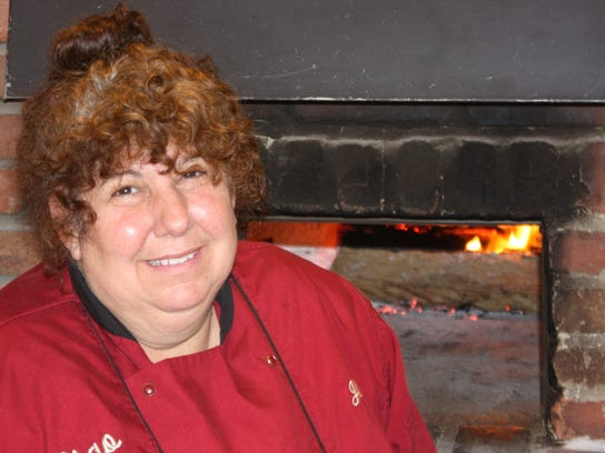 Chef-owner Jill Bacus in front of the wood-burning