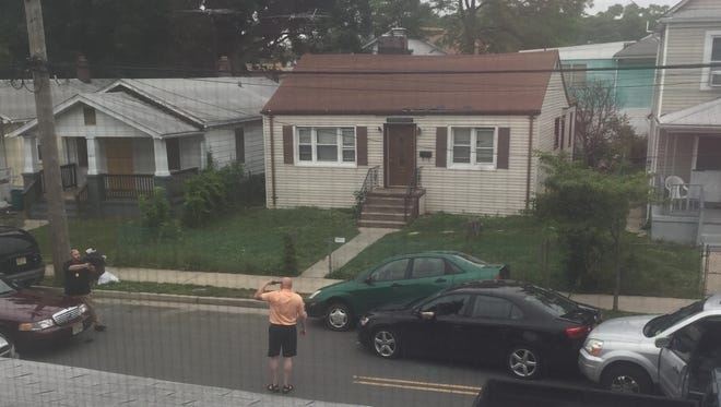 Philip Seidle, with his gun to his head, in a standoff with police on June 16, 2015 on Sewell Avenue in Asbury Park. A resident, Shenise Bellamy, took the photo from an upstairs bedroom. Lakayla Crumes' home is the tan house directly across the street.