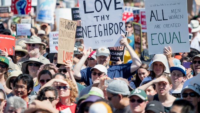 People hold up signs and shout while listening to speakers during a Rally Against Hate.