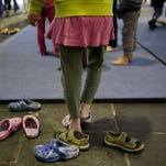 A girl takes of her shoes to attend an artistic program at a temporary emergency shelter for migrants, refugees and asylum seekers inside Hanger 1 of the former airport Tempelhof in Berlin, Wednesday, Dec. 9, 2015.
