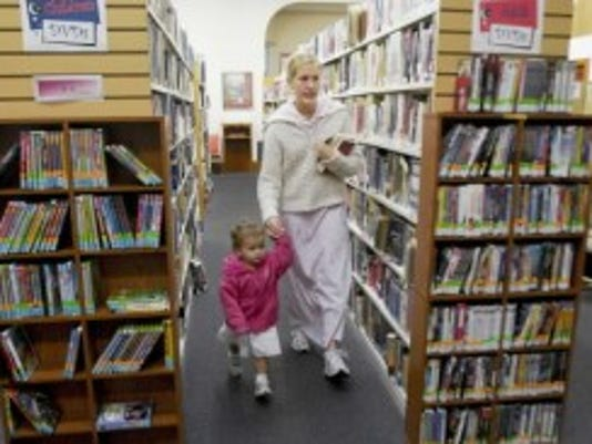 Abigail Nell leads her daughter. McKenzie, 19 months, down the rows of books at the East Berlin Community Library in 2007. (DAILY RECORD/SUNDAY NEWS -- FILE)