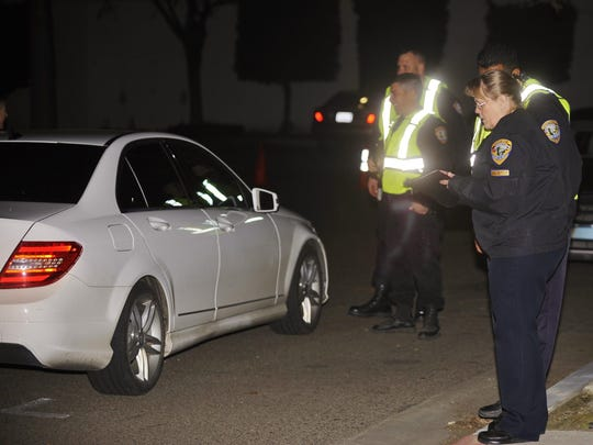 Barbara Smith keeps tracks of the vehicles stopped during Friday's DUI checkpoint.