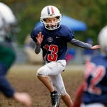 Juliette Haming, the only girl on the 5th grade football team at St. Agnes, plays against Holy Trinity on Saturday afternoon.  Oct. 3, 2015