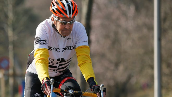In this March 18, 2015 file picture, U.S.  Secretary of State John Kerry rides his bicycle along the shore of Lake Geneva. Kerry was injured in May, while riding  in France.