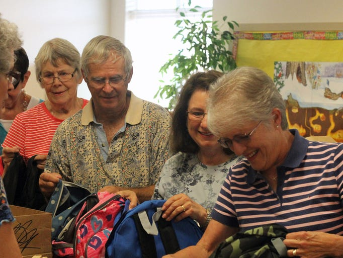 Linda Parker, right, smiles as she secures a ruler into a backpack for an elementary school-age child Saturday at Shepherd of the Hills United Methodist Church.Volunteers gathered Saturday to fill backpacks for the Backpacks 4 Kids program, which provides school supplies to underprivileged children in the Washington County School Board.