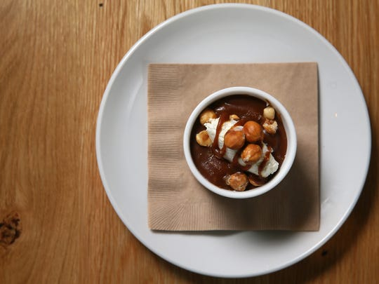 The butterscotch budino dessert, featuring caramel sauce, creme fraiche, hazelnuts and vanilla-scented malden sea salt, pictured, Tuesday, Oct. 31, 2017, at Harvest Pizzeria on Elm Street in Over-the-Rhine.