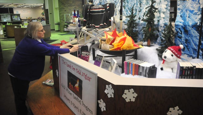 Kay Herold, a librarian at the Crestline Public Library, arranges books for the Winter Reading Program beginning at the library.