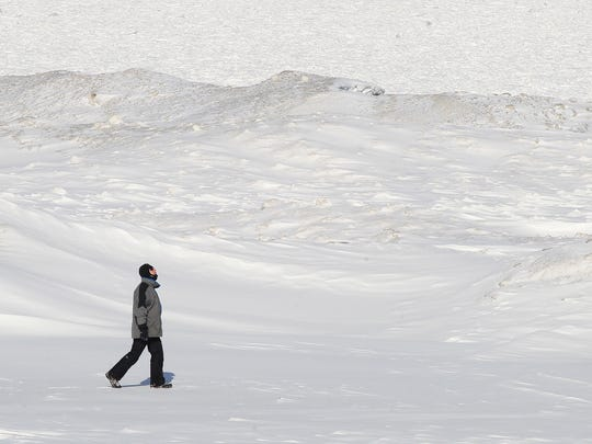 Tom Cook of Greece soaks up the sunshine while braving the single-digit temperatures Monday as he walks along the frozen shoreline of Lake Ontario near Durand-Eastman Park.