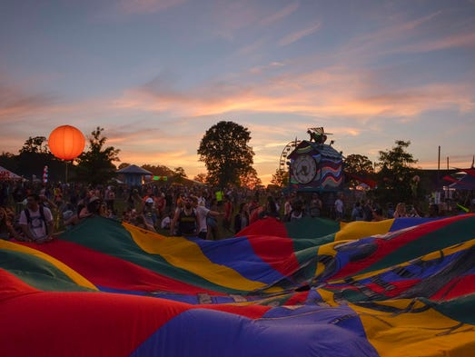 Guests play with a large parachute at the Bonnaroo