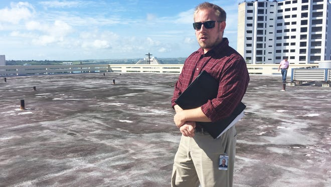 Micronesia Renewable Energy Operations Manager Sean Carbonneau stands on top of the third story roof of the Guam Memorial Hospital where that the company will place 432 solar panels on Oct. 20, 2017.
