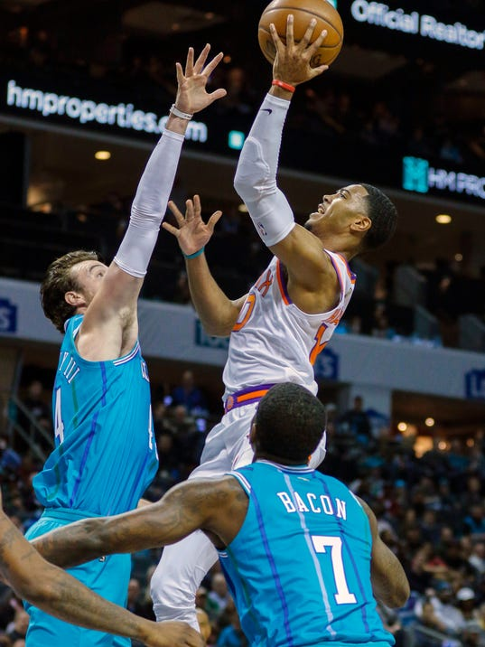 Phoenix Suns guard Shaquille Harrison, right, shoots over Charlotte Hornets forward Frank Kaminsky as Charlotte Hornets forward Dwayne Bacon looks on in the first half of an NBA basketball game in Charlotte, N.C., on Saturday, March 10, 2018. (AP Photo/Nell Redmond)