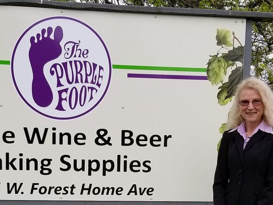 The Purple Foot owner Karen Lau with her sign out front