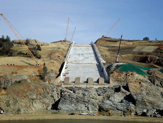 Cranes sit on the sides of the Oroville Dam spillway