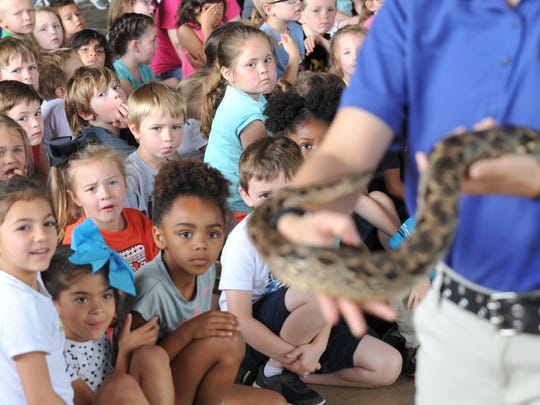 Dallas Zoo animal outreach specialist Dianne Rivas displays, Onja, a Dumeril's ground boa to a group of children and parents Tuesday morning during their visit to the River Bend Nature Center. The Dallas Zoo will be visiting River Bend Nature Center through the 3rd of May.