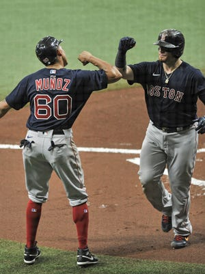 Boston's Yairo Munoz, left, congratulates Christian Vazquez, right, after scoring on Vazquez's two-run home run off Tampa Bay's Charlie Morton during the first inning of Sunday's win.