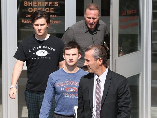Alex, left, and Colin Rideout leave the Monroe County Sheriff's Office after posting bail in July. With them at right is attorney Matthew Parrinello.