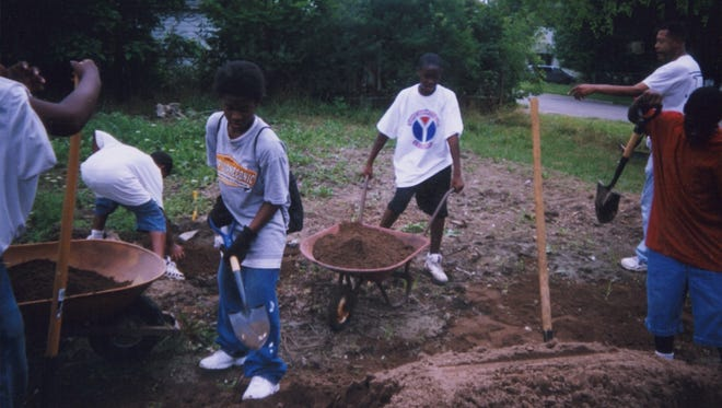 """Kids at work fixing up vacated property in Flint, Michigan as part of """"greening efforts"""" for study"""