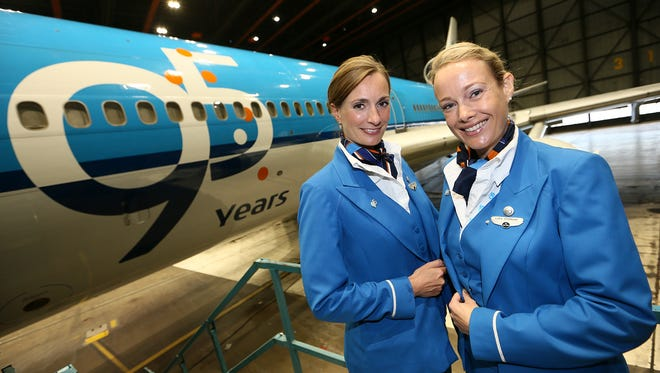 KLM attendants pose in front of a 95th anniversary logo that the airline added to one its MD-11 aircraft.