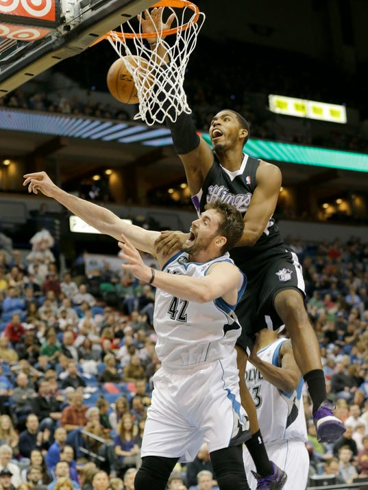 Sacramento Kings forward Jason Thompson, top, lands on Minnesota Timberwolves forward Kevin Love (42) as they battle for a rebound during the first quarter of an NBA basketball game in Minneapolis, Sunday, March 16, 2014. (AP Photo/Ann Heisenfelt)