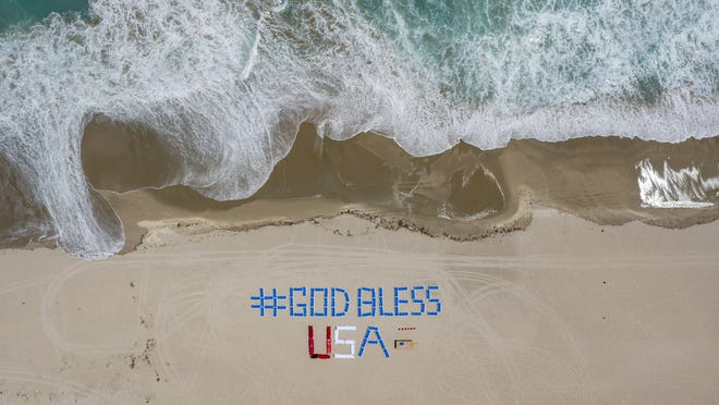 """Beach chairs spell out """"God Bless USA"""" on the beach Thursday outside the Palm Beach Marriott Singer Island Resort. The staff spells out a new positive phrase every day for residents and guests. Palm Beach County beaches are closed and residents have been ordered to stay home to slow the spread of the coronavirus."""