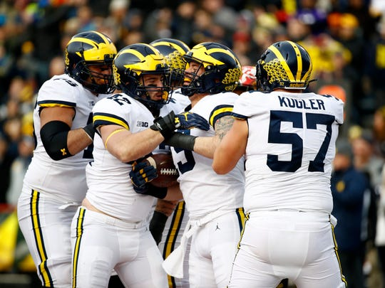 Michigan fullback Henry Poggi, second from right, celebrates