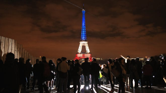 The Eiffel Tower is illuminated in Red, White and Blue Monday in honor of the victims of Friday's terrorist attacks in Paris.