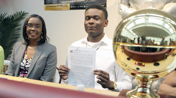 Mount Vernon senior basketball player Greg Calixte, right, with his mother Elna signs a National Letter of Intent to play basketball at George Mason University at Mount Vernon High School on Friday, April 21, 2017.