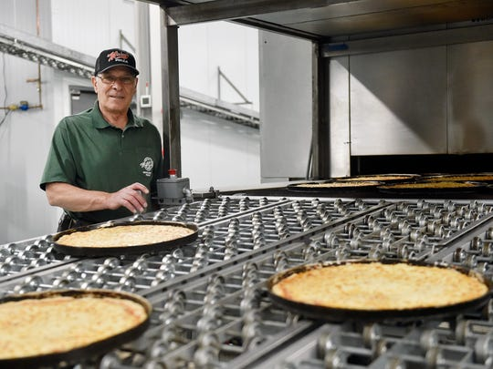 Founder and president Mickey Pantano stands for a portrait at the conveyor belt carrying freshly baked pizzas out of the oven at Mickey's Wholesale Pizza in Loganville.