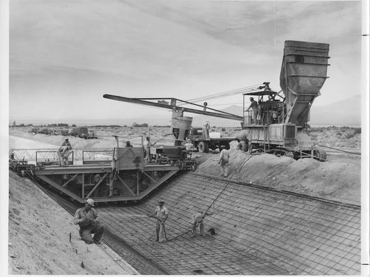During the construction of the Coachella Canal in 1946, a worker sprinkles the area as a paver machine lines the wasteway. The Salton Sea can be seen in the distance. Bureau of Reclamation photo taken by Harry W. Myers.