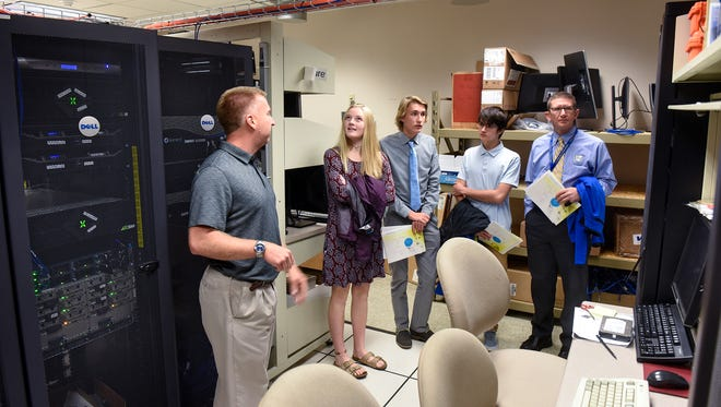 Cathedral High School students Maggie Voss, Tabler Elliott and Alex Florea take a tour of the server room at the Stearns County government center Tuesday, Oct. 17, in St. Cloud.