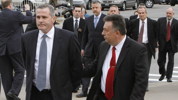 Dan Lynch, a former Siemens sales executive, front left, is escorted from the Attorney General's office to the Rochester Police Dept. for booking as part of the LDC scandal investigation Nov. 6, 2013.