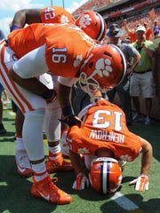 Clemson wide receiver Hunter Renfrow (13) lies on the ground as teammates tight end Jordan Leggett (16) and defensive lineman Christian Wilkins (42) check on him after he caught a touchdown against Troy on Sept. 10 at Clemson's Memorial Stadium. Renfrow broke a bone in his hand on the play.