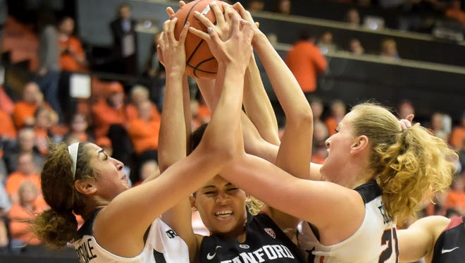 Oregon State forward Taya Corosdale, left, and center Marie Gulich, right, battle for a rebound with Stanford's Kaylee Johnson in the first half.