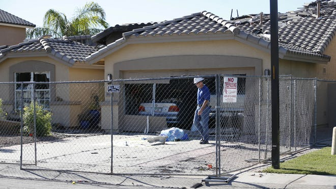 Investigators look through wreckage at a house after a plane crash in Gilbert on Sept. 18, 2016. Nobody was killed.