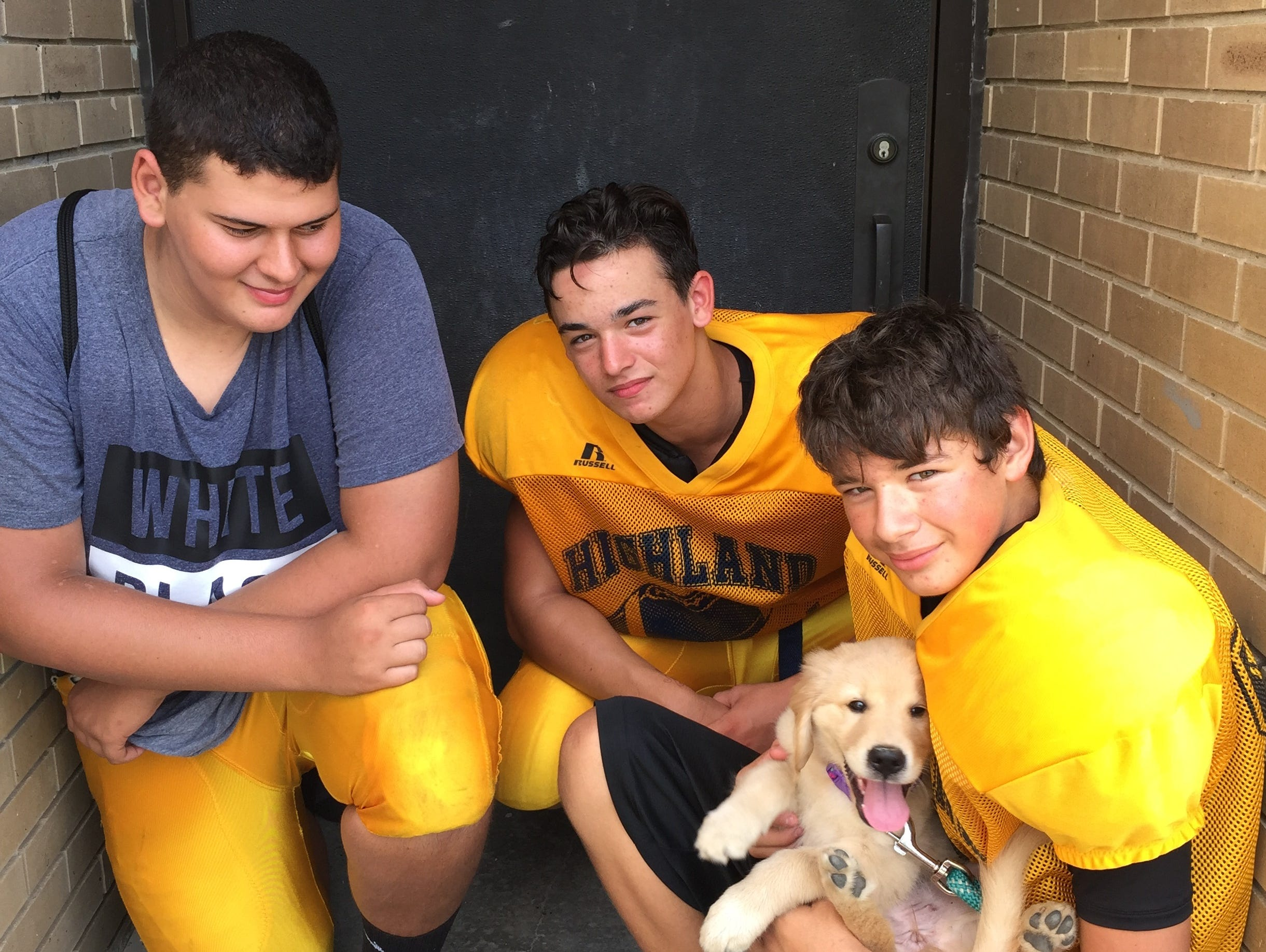 Highland football players James Keller and Adam Albright with Christian Rozzi and his dog, Freedom.