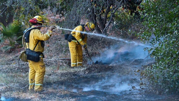 Firefighters water down burning embers from an overnight