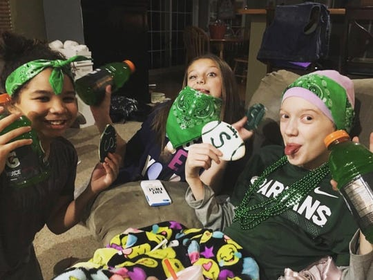 McKenna Schummer, right, passed away March 6 after a two-year fight with bone cancer. The 11-year-old was a hardcore MSU fan who drank green Gatorade while watching games. Miles Bridges dedicates this season to her.
