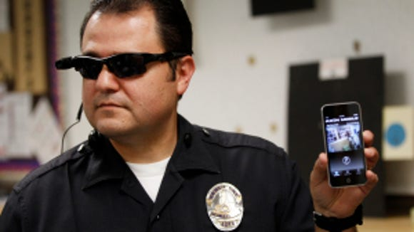 Los Angeles Police Sgt. Daniel Gomez demonstrates a video feed from his camera into his cellphone during a on-body camera demonstration for the media, in Los Angeles. (AP Photo/Damian Dovarganes,File)