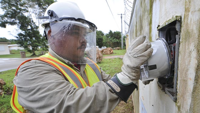 In this file photo, Apex CoVantag installer Derek Cruz inserts a new smart meter into a meter box after replacing the old meter at a Yigo residence. Because of smart meters, GPA will be laying off eight employees.