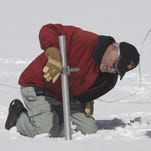 Frank Gehrke  checks the snow pack depth while performing the snow survey at Phillips Station near Echo Summit on March 30.
