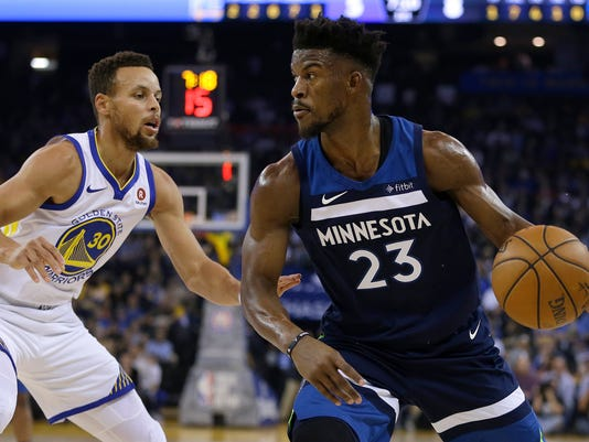 Minnesota Timberwolves' Jimmy Butler, right, drives the ball against Golden State Warriors' Stephen Curry (30) during the first half of an NBA basketball game Wednesday, Nov. 8, 2017, in Oakland, Calif. (AP Photo/Ben Margot)