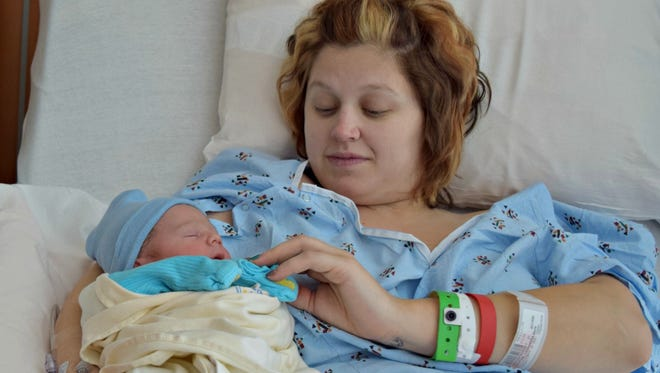 Cassie McIntire holds her new son Ayden, who was the first child born in Springfield in 2016.