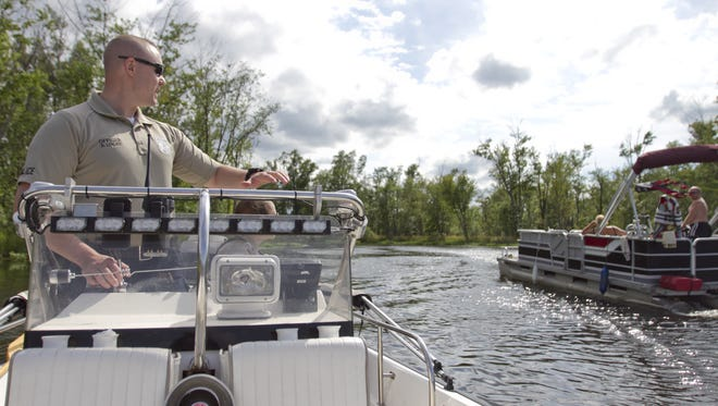 Hamburg Township Police Department Officers Steve Locke (at helm) and Kim Leeds greet fellow boaters on the Chain of Lakes  in Hamburg Township as the officers from the run a routine patrol of the waterway.